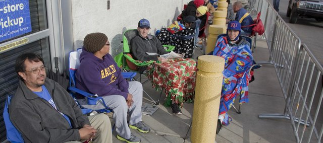 "In the foreground from left, Marei Spaola, Leandra Galindo and William Robbins, all of Lawrence, and Brenton Swart, Wichita, join other shoppers to spend their Thanksgiving day waiting in line at Lawrence's Best Buy store for the midnight Black Friday opening. Spaola and Galindo were in line at 6 a.m. Thursday, while Robbins drove down to Wichita to pick up his friend Swart, to return to Lawrence to wait in line. ""The lines at Best Buy in Wichita were too long,"" Swart said. Specials on TVs and computers were the big attraction."