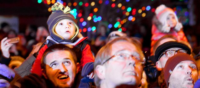 Kamden Robson, 15 months, watches the spectacle of Santa's arrival on the roof of Weaver's as he sits on his the shoulders of his uncle Taylor Stuart, Lawrence, during the annual Downtown Holiday Lighting Ceremony and Santa Rescue, Friday, Nov. 23, 2012 outside Weaver's Department Store, 901 Massachusetts. Nick Krug/Journal-World Photo