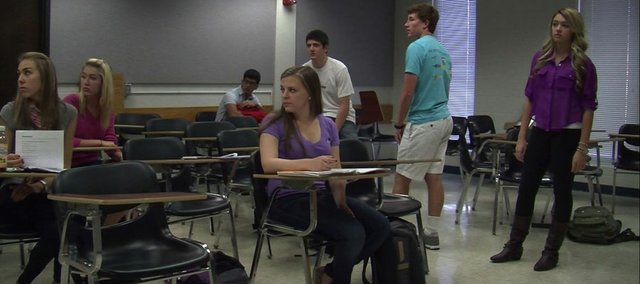 "In this scene from ""Té Buffet of Life,"" KU freshmen in a Mount Oread Scholars ""living learning community"" program portray high school students. The film, a high-school romantic comedy, was written, directed, produced, acted and edited by a group of 20 students in the program. Scenes at the ""high school"" were filmed in Wescoe Hall, where the group meets for a seminar."
