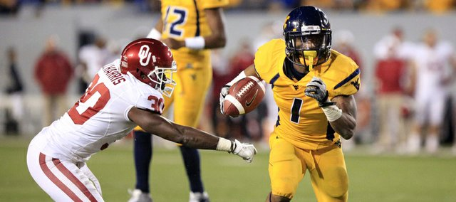 West Virginia wide receiver Tavon Austin (1) slips past Oklahoma's Javon Harris (30) for a rushing touchdown on Nov. 17 in Morgantown, W.Va. Austin ran for 344 yards against the Sooners, a feat Kansas University coach Charlie Weis hopes he won't repeat against the Jayhawks on Saturday.