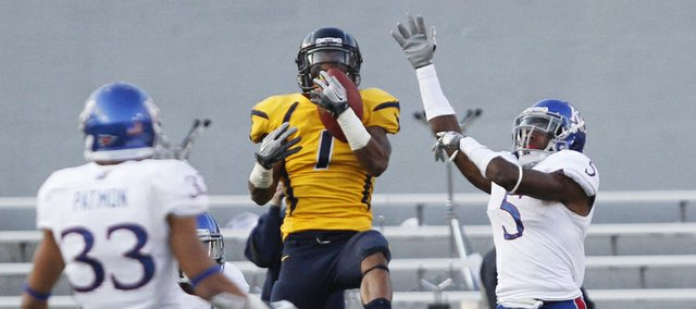 West Virginia receiver Tavon Austin (1) grabs a deep pass in front of KU defender Greg Brown and Tyler Patmon (33) in KU's 59-10 loss Saturday against West Virginia University in Morgantown, W.Va.