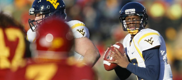 West Virginia quarterback Geno Smith drops back to pass against Iowa State in this file photo from Nov. 23 in Ames, Iowa. The one-time Heisman Trophy front-runner will try to lead the Mountaineers over Kansas today.