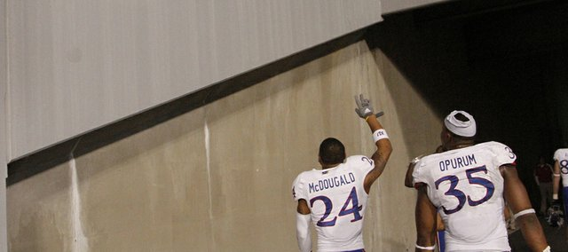 KU seniors Bradley McDougald (24) and Toben Opurum (35) wave to KU fans as they leave the field following KU's 59-10 loss Saturday against West Virginia University in Morgantown, W.Va.