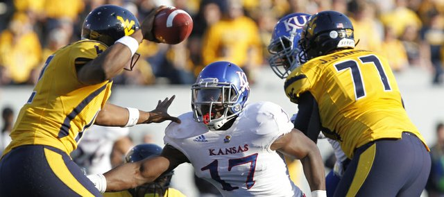 Kansas linebacker Tunde Bakare (17) pursues West Virginia quarterback Geno Smith (12) in KU's last football game Saturday against West Virginia University in Morgantown, W.Va.
