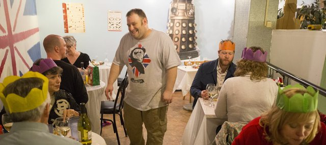 Matt Poulton, owner of Queen Lizzy's Fish and Chips Shop, checks on patrons as they enjoy a British Christmas Dinner on Sunday at the restaurant. The menu included roasted parsnips, turkey, ham, stuffing, Brussels sprouts, Yorkshire pudding and figgy pudding.