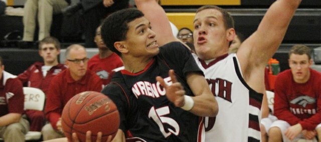 Lawrence High School sophomore Anthony Bonner (15) drives to the basket around 6&#39;5&quot; defender Tyler Anderson (40) in the Lions 55-47 loss to Lees Summit North, Thursday at Blue Valley High school in the Blue Valley Shootout tournament.