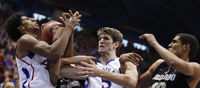 Kansas forward Kevin Young wrestles for the ball with Colorado defender Andre Roberson (21) teammate Jeff Withey and CU forward Josh Scott (40) during the second half on Saturday, Dec. 8, 2012 at Allen Fieldhouse.