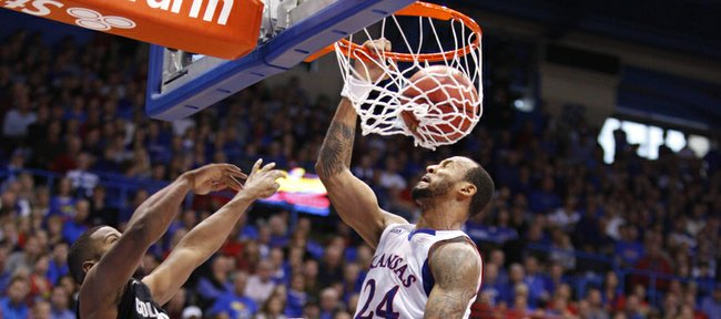 Kansas guard Travis Releford extends to dunk over Colorado defender Jeremy Adams during the first half on Saturday, Dec. 8, 2012 at Allen Fieldhouse. At right is KU forward Jamari Traylor.