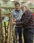 George Renault, of Lawrence, left, picks out a piece of aspen tree wood that Paul LaGue, of Tonganoxie, right, will carve into a hiking stick, at Saturday's Holiday Farmers' Market, which is in its 25th year.