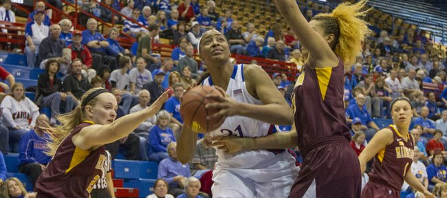 Kansas' Carolyn Davis (21) makes a move in the low post around Micaella Riche, right, during Kansas' game against Minnesota Sunday afternoon at Allen Fieldhouse. The 65-53 win over the Minnesota improved Kansas' record to 7-0 on the season.