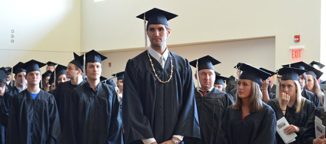 Kansas University center Jeff Withey, center, stands among the December KU graduates receiving information about the graduation ceremony on Sunday, Dec. 9, 2012, at the Lied Center.