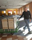 Jim Wilkins, with the city public works department, wheels out a cart of purchased remainder items at the former Borders bookstore Monday. The building is being readied for the Lawrence Public Library to move in to temporarily during the library's expansion project.