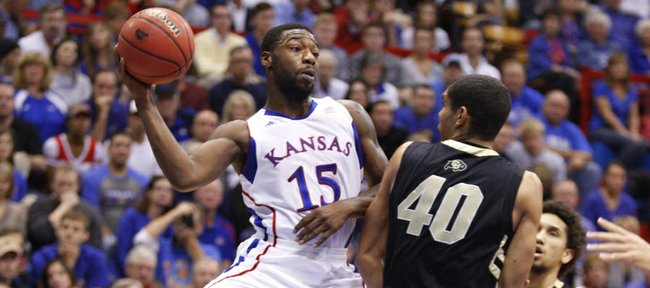 Kansas guard Elijah Johnson throws a pass around Colorado forward Josh Scott during the first half on Saturday, Dec. 8, 2012 at Allen Fieldhouse.