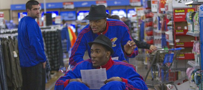 Kansas freshmen Ben McLemore, back, and Jamari Traylor use a cart to shop on Thursday, Dec. 13, 2012, during the Jayhawks' holiday shopping excursion to Wal-Mart.