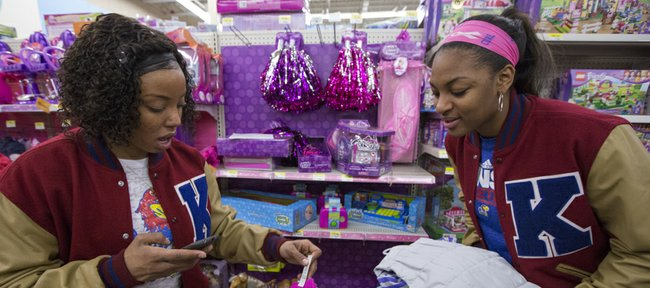 Members of the Kansas women's basketball team, CeCe Harper, left, and Bunny Williams, add up prices while debating whether to choose pompoms or fairy wings as they shop at Wal-Mart on South Iowa Street on Saturday, Dec. 15, 2012, as part of the Salvation Army Angel Tree program.