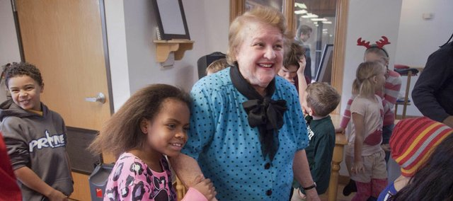 Raintree Montessori student Mari Risley, gives a hug to Thelma Sophocleous, who has worked at Rainteee Montessori School for more than 30 years.