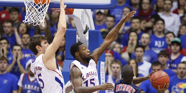Kansas defenders Elijah Johnson (15) and Jeff Withey swoop in to defend against a shot by Richmond guard Kendall Anthony during the first half on Tuesday, Dec. 18, 2012 at Allen Fieldhouse.