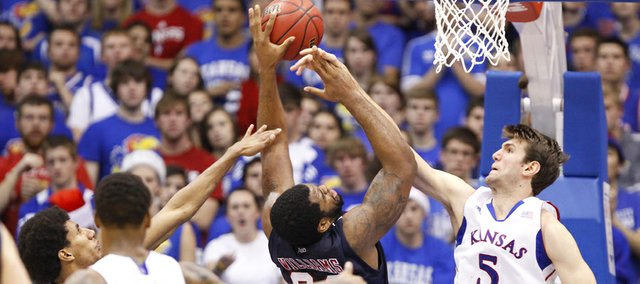 Kansas center Jeff Withey deflects a shot by Richmond forward Derrick Williams during the second half on Tuesday, Dec. 18, 2012 at Allen Fieldhouse.