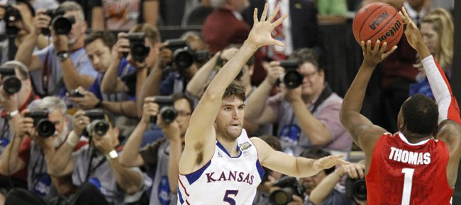 Jeff Withey (5) jumps out to defend a shot by Deshaun Thomas (1) and over Aaron Craft, during the second-half of KU's 64-62 win over Ohio State to put the Jayhawks the Championship game agains Kentucky, Monday night.