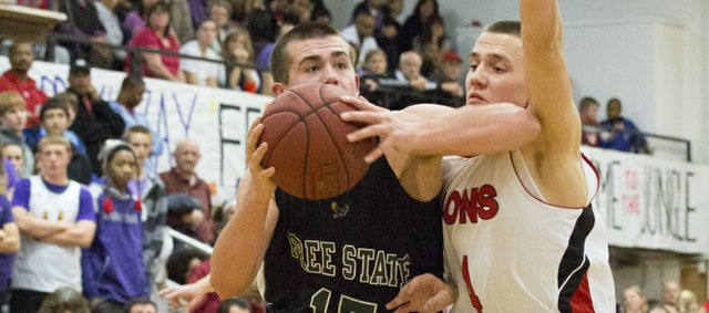 Free State's Keith Loneker (14) drives past Austin Abbott during Lawrence High's game against Free State, Friday, Dec. 14, 2012 at LHS.