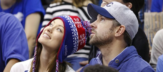Actor Jason Sudeikis and actress Olivia Wilde watch the video board during the second half on Saturday, Dec. 29, 2012 at Allen Fieldhouse.
