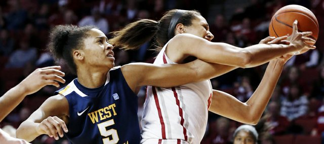 West Virginia's Averee Fields (5) reaches around Oklahoma's Nicole Griffin (4) for a rebound during the second half of their NCAA college basketball game, Wednesday, Jan. 2, 2013, in Norman, Okla. Oklahoma won 71-68.