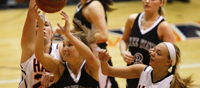 Free State guard Kennedy Kirkpatrick goes to the bucket against Olathe East defenders Audrey Markway (22) and Regan Stone (10) during the first half on Friday, Jan. 4, 2012 at Olathe East High School. Nick Krug/Journal-World Photo