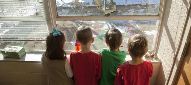 St. John Catholic School students, from left, Payton Hoover, Nicholas Goos, Luke Cast and Tristan Prier, check out the progress on a new addition at the school, 1208 Kentucky St., from the principal's office on Friday.