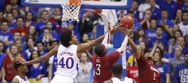 Kansas forward Kevin Young fights for a rebound with Temple players Anthony Lee and Khalif Wyatt during the first half on Sunday, Jan. 6, 2013 at Allen Fieldhouse.