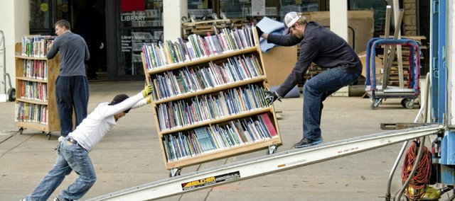 Khoi Pham, left, and Michael Drier, both with Beltman Group, of Lenexa, roll book carts into a moving truck on Monday. The move to the former Borders bookstore at Seventh and New Hampshire streets will take about two weeks.