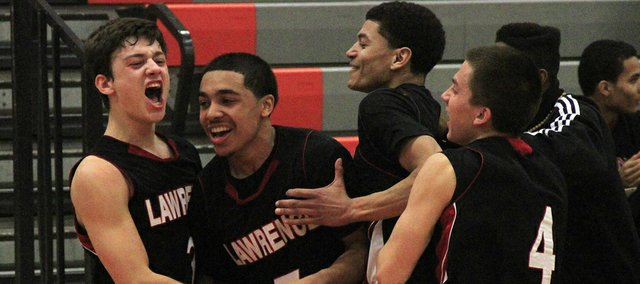 Lawrence High senior Jake Mosiman, left, is mobbed by teammates Justin Roberts (5), Anthony Bonner (15) and Austin Abbott (4) after shooting a buzzer-beating three-pointer to beat Shawnee Mission Northwest, 55-54, on Tuesday, Jan. 8, 2012, in Shawnee.