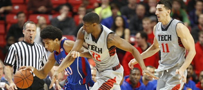 Kansas forward Kevin Young is fouled by Texas Tech forward Jordan Tolbert after grabbing a steal during the first half on Saturday, Jan. 12, 2013 at United Spirit Arena in Lubbock, Texas. At right is Texas Tech forward Dejan Kravic.