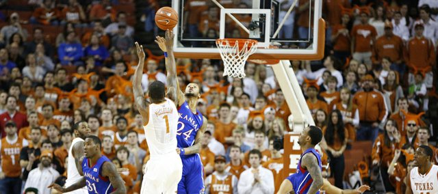 Texas guard Sheldon McClellan puts up a shot over Kansas guard Travis Releford during the first half on Saturday, Jan. 19, 2013 at Frank Erwin Center in Austin, Texas.