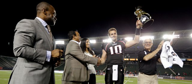 National team quarterback Dayne Crist (10) of Kansas holds up the trophy as head coach Dick Vermeil, right, and NFLPA Executive Director DeMaurice Smith celebrate after the NFLPA Collegiate Bowl on Saturday, Jan. 19, 2013 in Carson, Calif. (Ric Tapia/AP Images for NFLPA)