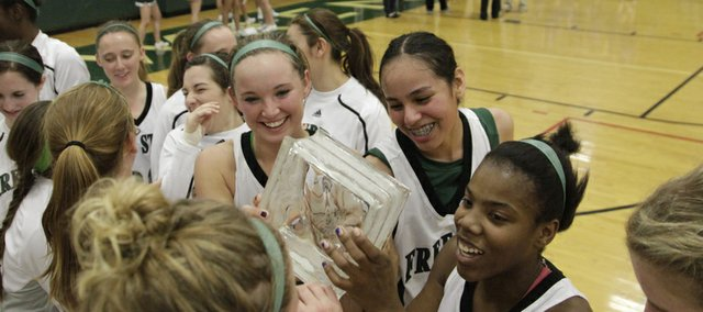 At center from left, Kennedy Kirkpatrick, Mille Shade and A'Liyah Rogers, hold the trophy after the Free State Firebirds win over Washburn Rural in the championship game of the Firebirds Winter Classic Saturday at FSH.