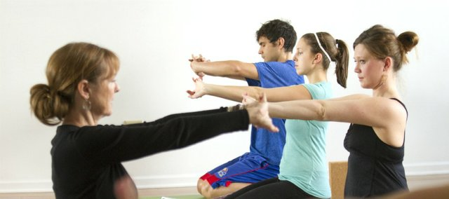 Francie Arnold, left, leads a class in her Heart Flow yoga class Jan. 17 at OmTree Shala yoga studio, 1405 Massachusetts St. In Lawrence, options abound for many types of yoga, depending on your interest, skill level and goals.