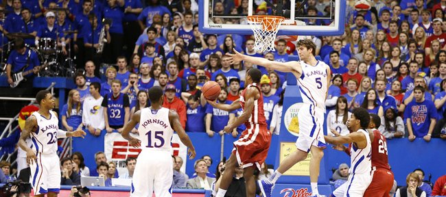 Kansas center Jeff Withey stretches to defend against a shot from Oklahoma guard Buddy Heild during the second half on Saturday, Jan. 26, 2013 at Allen Fieldhouse.
