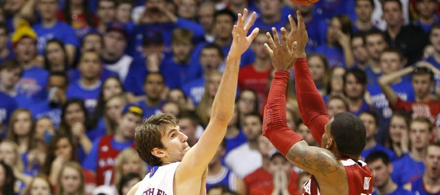 Kansas center Jeff Withey extends to defend against a shot from Oklahoma forward Romero Osby during the first half on Saturday, Jan. 26, 2013 at Allen Fieldhouse.