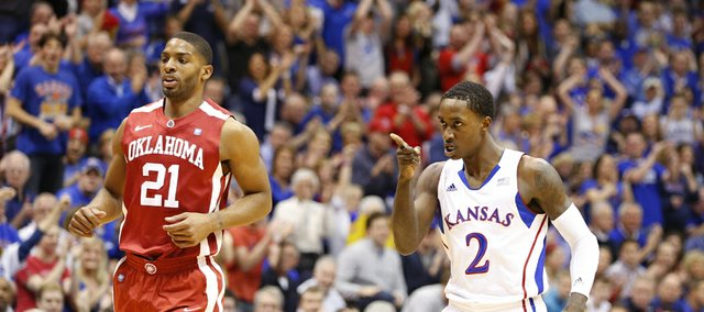 Kansas guard Rio Adams points to teammate Kevin Young after Young's breakaway dunk following a steal against Oklahoma during the first half on Saturday, Jan. 26, 2013 at Allen Fieldhouse. At left is Oklahoma guard Cameron Clark.
