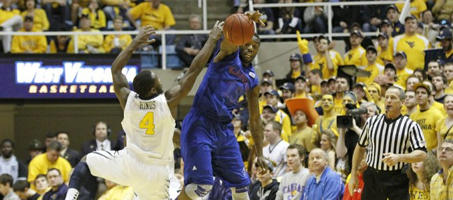 Kansas guard Elijah Johnson goes for a steal against West Virginia's Jabarie Hinds (4) in the Jayhawks' game against the Mountaineers on Monday night in Morgantown, W.Va.