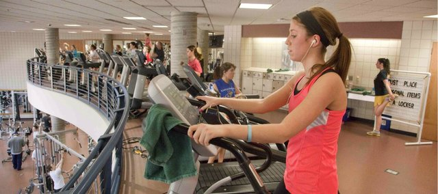 Morgan Cross, 19, a Kansas University sophomore from Overland Park, works out Monday at Ambler Student Recreation Fitness Center on the KU campus. The rec center is available not only to students — faculty and staff are offered special rates to use the facilities as one of KU's employee wellness incentives.