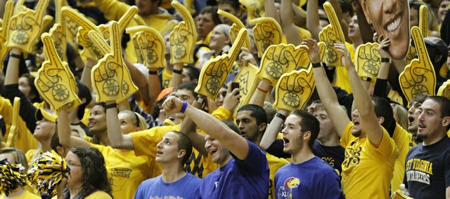Three Kansas fans in a sea of West Virginia fans cheer for the Jayhawks during Jayhawks 61-56 win against the Mountaineers Monday night at West Virginia University. From left are Jay Gould, Kurt Honas and Nick Dorsey, all from Wichita.