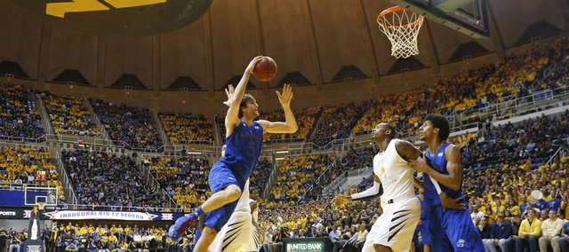 Jeff Withey (5) shoots a hook shot around a defender as Kevin Young (40) positions for a rebound in the Jayhawks 61-56 win against the Mountaineers Monday night at West Virginia University.