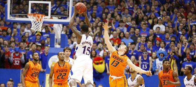 Kansas guard Elijah Johnson elevates to throw a pass as Oklahoma State guard Phil Forte defends during the second half on Saturday, Feb. 2, 2013 at Allen Fieldhouse.