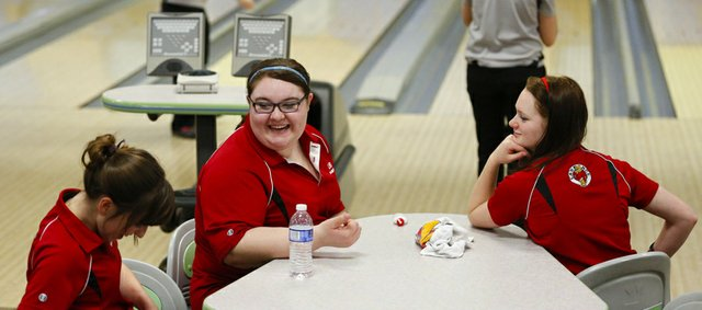 Lawrence High bowlers Zoe Reed, left, senior, Kierstan Warren, junior, and Rebecca McNemee, senior, have a laugh at the table while waiting for their turns to roll on Thursday, Feb. 7, 2013 at Royal Crest Lanes.