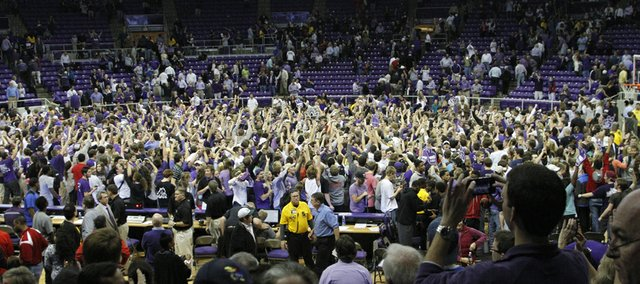 TCU fans flood the floor of the Daniel-Meyer Coliseum after the Horned Frogs defeated the Jayhawks, 62-55, Wednesday at TCU in Fort Worth, Texas.