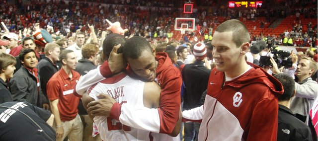 Oklahoma players Amath M'Baye hugs teammate Cameron Clark as the Sooners celebrate their 72-66 win over Kansas on Saturday, Feb. 9, 2013 at Noble Center in Norman, Oklahoma.