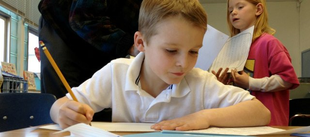 Jude Godfrey, a first-grader at Saint John Catholic School, works on a final draft of a story in a Monday afternoon writing workshop. Behind him, volunteer Tom Mach helps another student edit her writing.