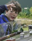 Ian Murphy, 8, Lawrence, counts the number of cars on a train as it passes him by at the 12th annual Lawrence Model Railroad show and swap meet Saturday, Feb. 16, at the Douglas County Fairgrounds.