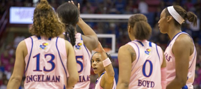"Kansas senior guard Angel Goodrich, center, is congratulated by teammate Bunny Williams during Kansas' annual ""Jayhawks for a Cure"" cancer awareness game against Oklahoma, Sunday, Feb. 17, 2013 at Allen Fieldhouse. Goodrich became Kansas' all time assist leader, scoring 10 assists against Oklahoma and pushing her career total to 687."